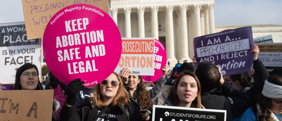 "Pro-choice activists hold signs alongside anti-abortion activists participating in the ""March for Life,"" an annual event to mark the anniversary of the 1973 Supreme Court case Roe v. Wade, which legalized abortion in the US, outside the US Supreme Court in Washington, DC, January 18, 2019. (SAUL LOEB/AFP/Getty Images)"