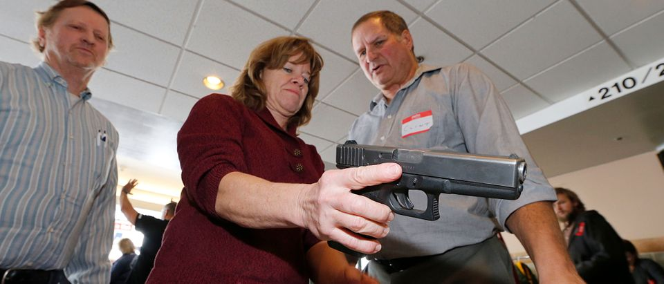 A Utah teacher is shown how to handle a handgun by instructor Clint Simon (R), at a concealed-weapons training class to 200 Utah teachers on December 27, 2012 in West Valley City, Utah. (Photo by George Frey/Getty Images)