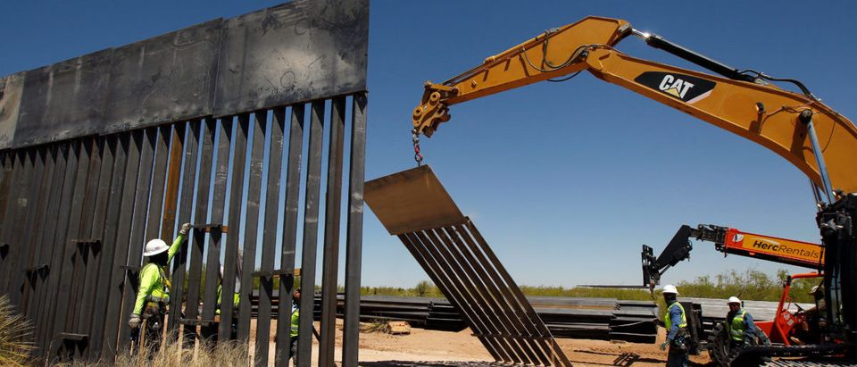Construction workers are seen next to heavy machinery while working on new bollard wall in Santa Teresa, New Mexico, as seen from the Mexican side of the border in San Jeronimo, on the outskirts of Ciudad Juarez, Mexico April 23, 2018. REUTERS/Jose Luis Gonzalez