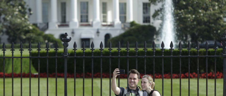 Tourists take selfies by the original South Lawn security fencing at the White House in Washington before anti-climb perimeter fencing installation in Washington