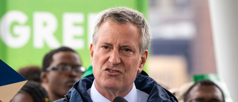 New York City Mayor Bill de Blasio holds up a copy of 'One NYC 2050' as he speaks the city's response to climate change at Hunters Point South Park, April 22, 2019 in the Queens borough of New York City. (Photo by Drew Angerer/Getty Images)