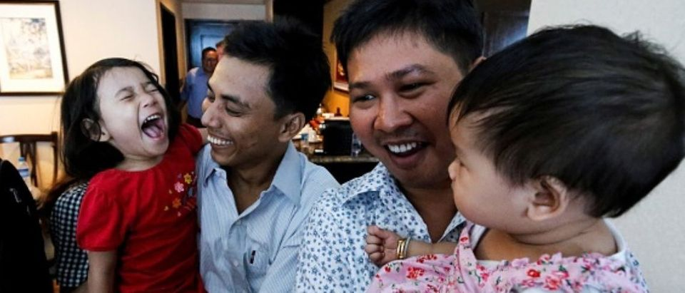 TOPSHOT - Reuters journalists Wa Lone (R) and Kyaw Soe Oo celebrate with their children after being freed freed from Insein prison after a presidential amnesty in Yangon on May 7, 2019. - Two Reuters journalists who had been jailed for their reporting on the Rohingya crisis in Myanmar walked out of prison on May 7, freed in a presidential amnesty after a global campaign for their release. (Photo credit should read ANN WANG/AFP/Getty Images)