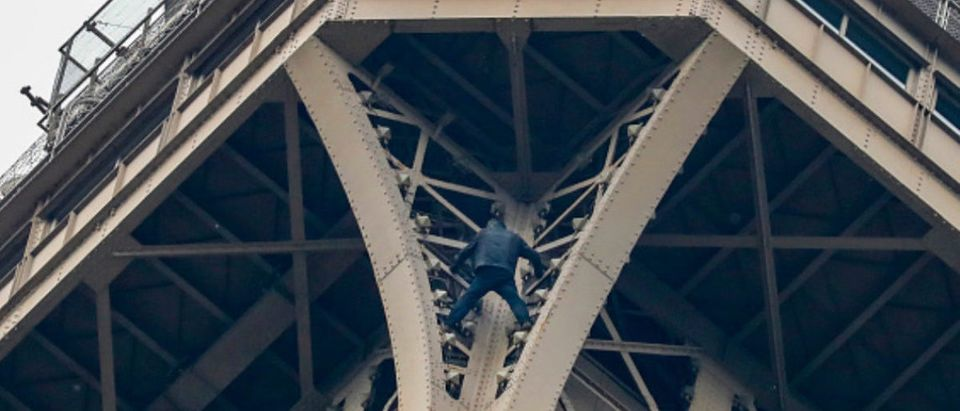 """A man (C) climbs up to the top of the Eiffel Tower, in Paris, without any protection, on May 20, 2019. - The Eiffel Tower was evacuated on May 20, 2019 in the afternoon after a person was spotted climbing up the Paris landmark, the company that operates the structure said. """"A climber has been spotted. It's the standard procedure: We have to stop the person, and in that case we evacuate the tower,"""" an official told AFP, adding that police were on the scene. (Photo credit: FRANCOIS GUILLOT/AFP/Getty Images)"""