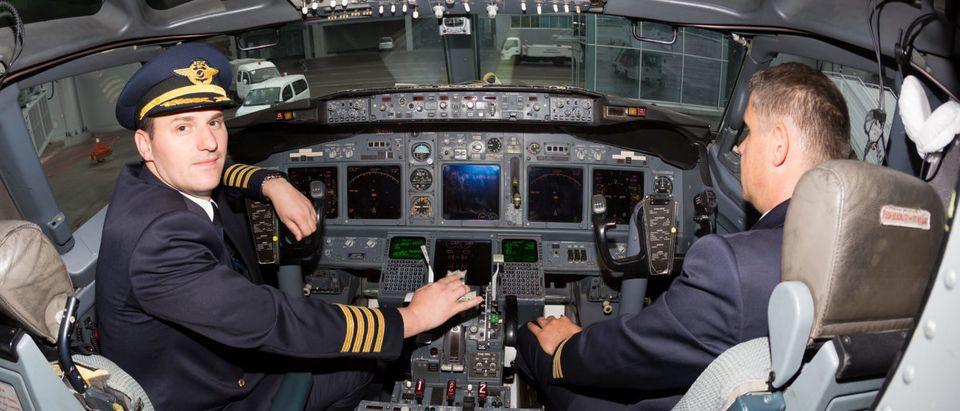 Kiev, Ukraine - MAY 14, 2015: Portrait of pilots in 737 cockpit. Shutterstock image via Dmitry Birin