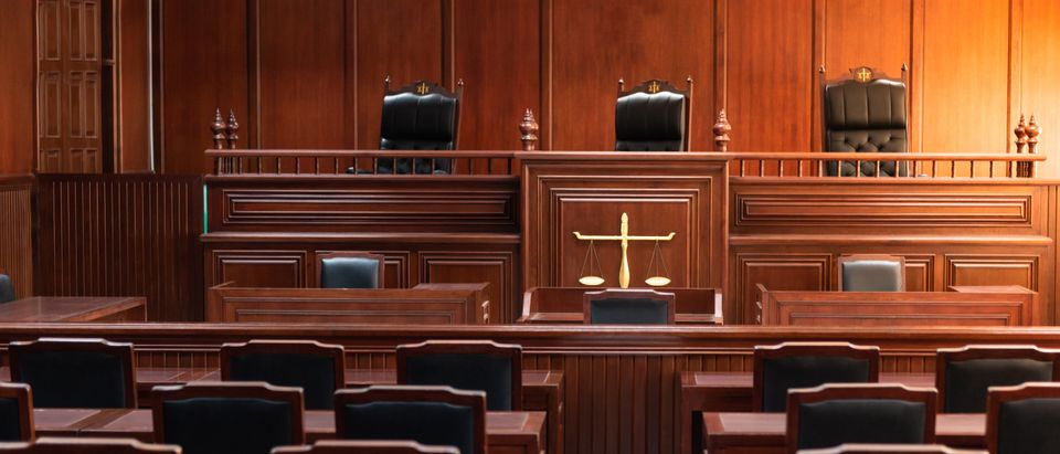 Red wood table and red chair in the justice court (Nirat.pix/Shutterstock)