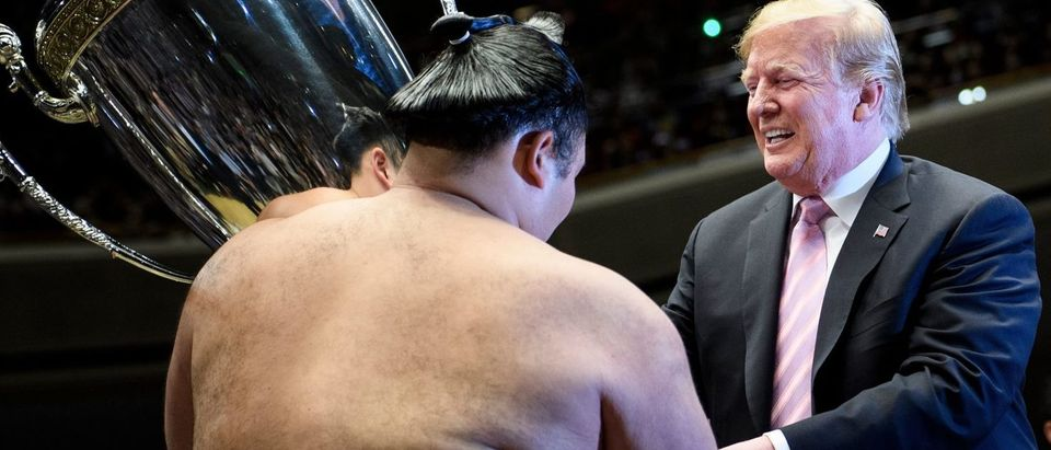 US President Donald Trump presents the President's Cup to sumo wrestler Asanoyama during the Summer Grand Sumo Tournament at Ryogoku Kokugikan Stadium in Tokyo on May 26, 2019. BRENDAN SMIALOWSKI/AFP/Getty Images