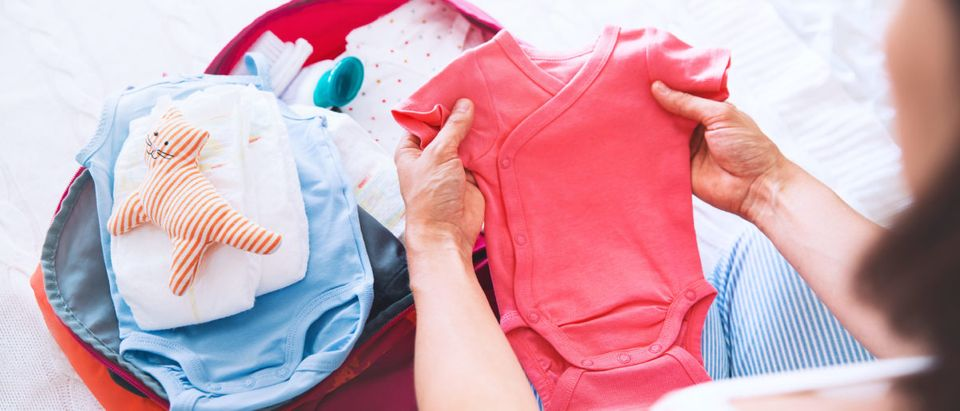 A woman folds baby clothes. Shutterstock image via Natalia Deriabina