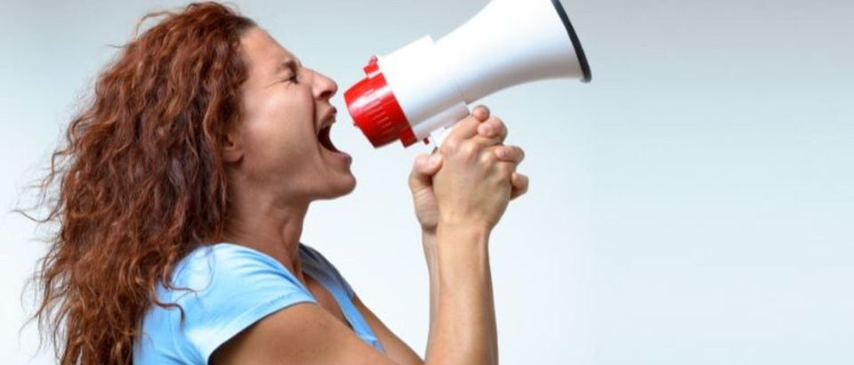 Young woman shouting into a megaphone, side view on white conceptual of a rally or protest - Image (Shutterstock/By michaelheim)