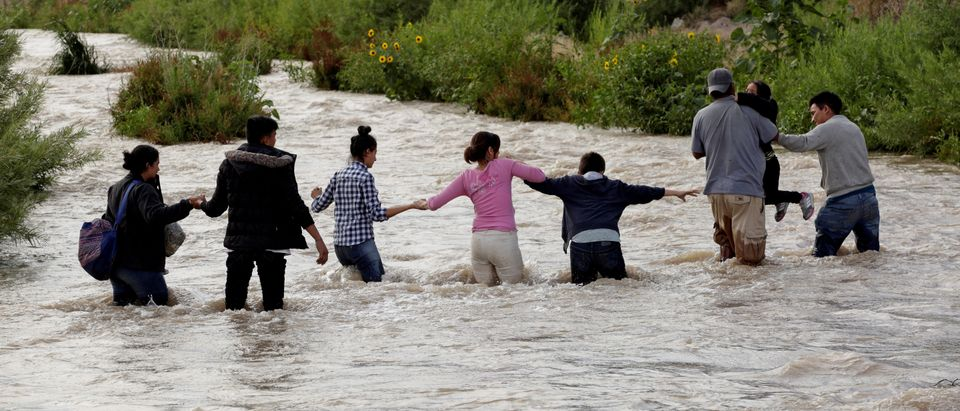FILE PHOTO: Migrants from Central America form a human chain to cross the Rio Bravo river to enter illegally into the United States to turn themselves in to request for asylum in El Paso, Texas, U.S., as seen from Ciudad Juarez, Mexico June 11, 2019. Picture taken June 11, 2019. REUTERS/Jose Luis Gonzalez