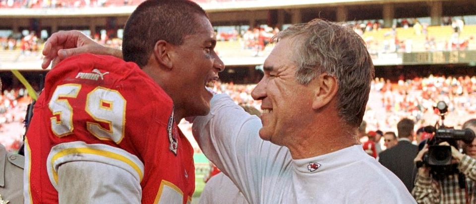 Kansas City Chiefs head coach Gunther Cunningham (R) hugs Chiefs linebacker Donnie Edwards afterthe Chiefs beat the San Diego Chargers 34-0 31 October 1999 at Kansas City's Arrowhead Stadium. (Photo credit: DAVE KAUP/AFP/Getty Images)