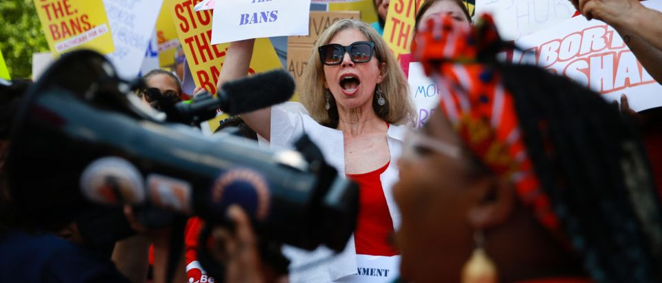 "A woman holds a clothes hanger with a sign that says ""stop the bans"" during a protest against recently passed abortion ban bills at the Georgia State Capitol building, on May 21, 2019 in Atlanta, Georgia. (Elijah Nouvelage/Getty Images)"