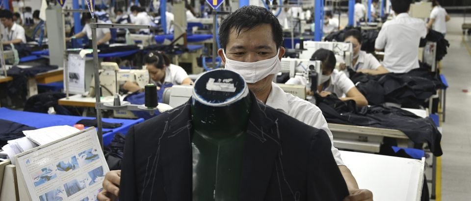 This photo shows garment factory workers making men's suits in a factory in Hanoi. Countries across Asia are hoping the US tariff squeeze on China will presage a permanent shift in manufacturing patterns as big name brands dodge the trade war in cheaper locations to make their goods. (MANAN VATSYAYANA/AFP/Getty Images)