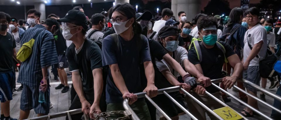 Protesters move a barricade during a clash at Legislative Council after a rally against the extradition law proposal at the Central Government Complex on June 10, 2019 in Hong Kong. (Photo by Anthony Kwan/Getty Images)