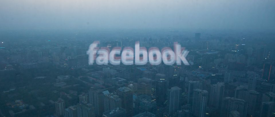 A photo taken on May 16, 2012 shows a computer screen displaying the logo of social networking site Facebook reflected in a window before the Beijing skyline. With investors hungry for Facebook shares ahead of a hotly anticipated offering, the social network unveiled a 25 percent increase in the number of shares to be sold at the market debut. AFP PHOTO / Ed Jones / Getty Images