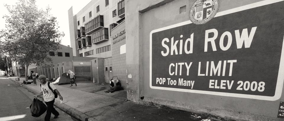 "A sign reading ""Skid Row"" is painted on a wall next to the Los Angeles Mission, September 22, 2014 in Los Angeles, California. Los Angeles' Skid Row contains one of the largest populations of homeless people in the United States. (Photo credit should read ROBYN BECK/AFP/Getty Images)"