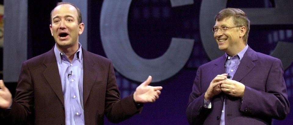 Amazon.com CEO Jeff Bezos (L) tells a joke with Mi