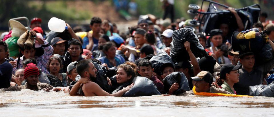 Central American migrants walk through the Suchiate river, the natural border between Guatemala and Mexico, in their bid to reach the U.S., as seen from Tecun Uman