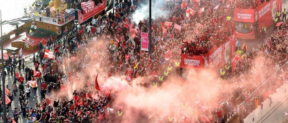 Football fans line the streets to see the Liverpool football team take part in an open-top bus parade around Liverpool, north-west England on June 2, 2019, after they won the UEFA Champions League final football match between Liverpool and Tottenham. - Liverpool's celebrations stretched long into the night after they became six-time European champions with goals from Mohamed Salah and Divock Origi to beat Tottenham -- and the party was set to move to England on Sunday where tens of thousands of fans awaited the team's return. The 2-0 win in the sweltering Metropolitano Stadium delivered a first trophy in seven years for Liverpool, and -- finally -- a first win in seven finals for coach Jurgen Klopp. (Photo credit: ANTHONY DEVLIN/AFP/Getty Images)