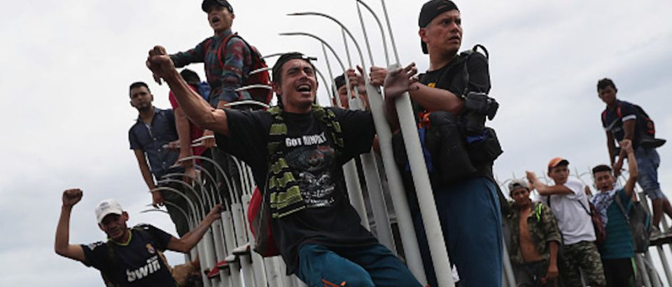 Members of the migrant caravan cheer as fellow immigrants clash with Mexican riot police at the border between Mexico and Guatemala on October 19, 2018 in Ciudad Tecun Uman, Guatemala