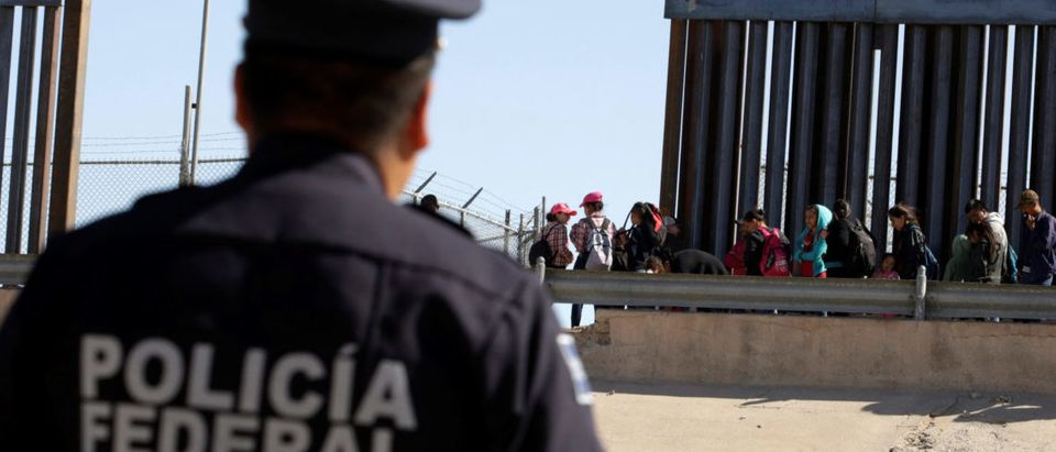 A Mexican police officer looks on as migrants queue to request asylum after crossing illegally into El Paso