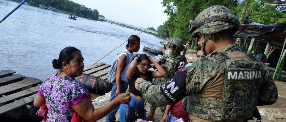 A member of the naval police checks the ID of a Guatemalan woman that crossed the Suchiate river on a raft from Tecun Uman, in Guatemala, to Ciudad Hidalgo, Mexico June 16, 2019. REUTERS/Jose Torres