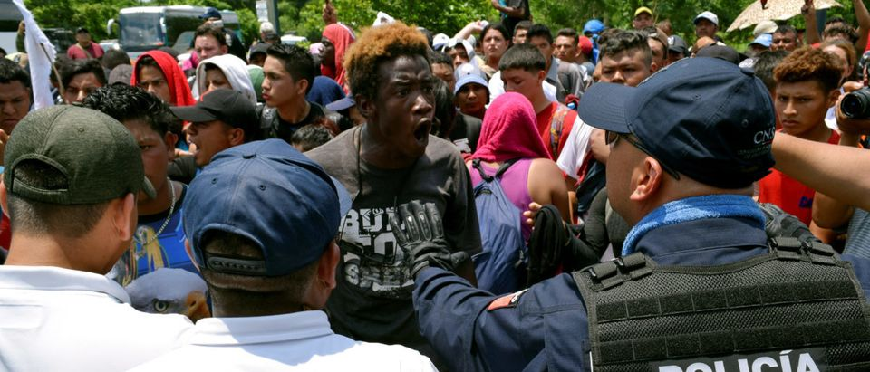 FILE PHOTO: A migrant argues with a federal police officer during a joint operation by the Mexican government to stop a caravan of Central American migrants on their way to the U.S., at Metapa de Dominguez