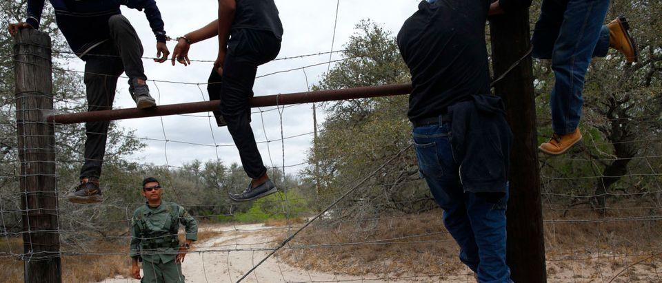 People are taken into custody by the U.S. Border Patrol near Falfurrias, Texas