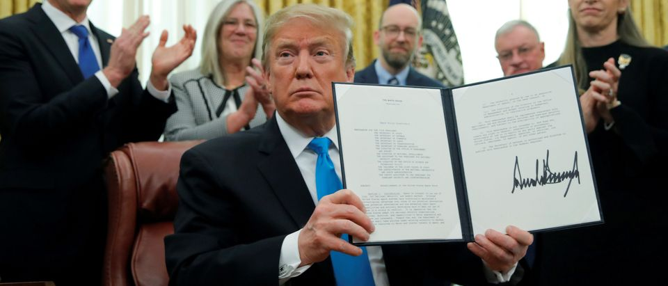 "U.S. President Donald Trump displays the ""Space Policy Directive 4"" after signing the directive to establish a Space Force as the sixth branch of the Armed Forces in the Oval Office at the White House in Washington, U.S., February 19, 2019. REUTERS/Jim Young."