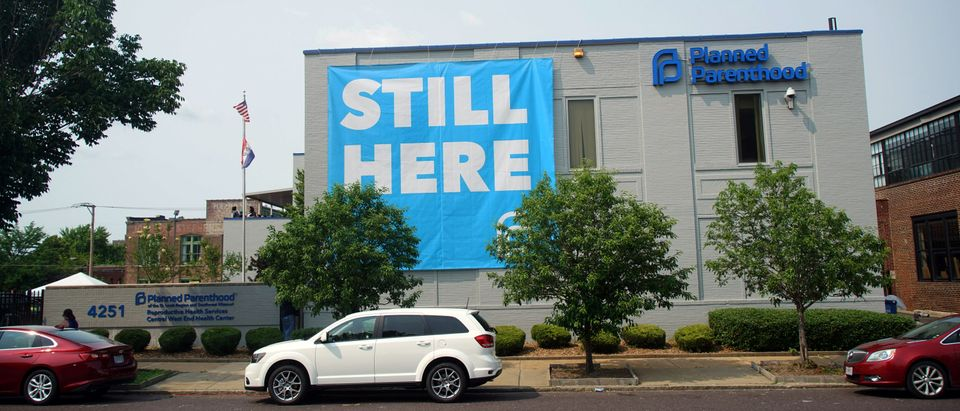"A banner stating ""STILL HERE"" hangs on the side of the Planned Parenthood Building after a judge granted a temporary restraining order on the closing of Missouri's sole remaining Planned Parenthood clinic in St. Louis"