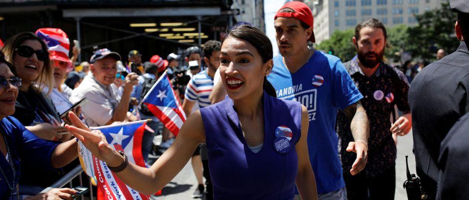 Representative Alexandria Ocasio-Cortez shakes hands on 5th Avenue at the annual Puerto Rican Day Parade in Manhattan, New York (Jose Alvarado Jr./REUTERS)