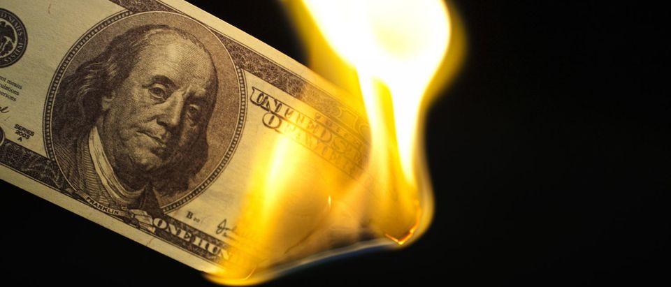 Image of one hundred bill burning on black background. (Korionov/Shutterstock)