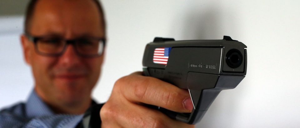 "An Armatix employee holds a smart gun by the company at the Armatix headquarters in Munich May 14, 2014. The gun is implanted with an electronic chip that allows it to be fired only if the shooter is wearing a watch that communicates with it through a radio signal. If the gun is moved more than 10 inches (25 cm) from the watch, it will not fire. A Maryland gun shop owner has dropped his plan to be the first in the United States to sell the so-called ""smart gun"" after a backlash that included death threats. REUTERS/Michael Dalder"