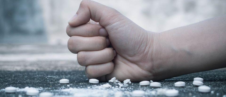 A hand crushes pills. Shutterstock image via Orawan Pattarawimonchai