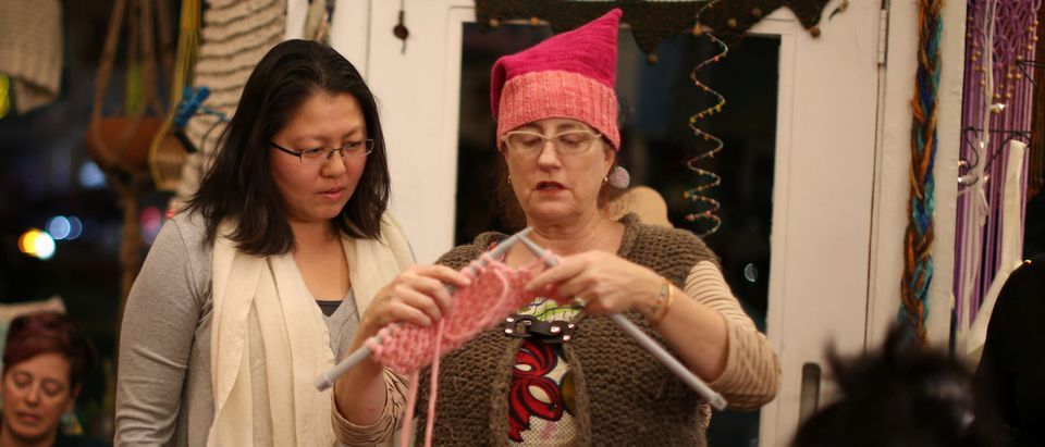 Molly Cleator teaches Crystal Ho to knit as they take part in the Pussyhat social media campaign to provide pink hats for protesters in the women's march in Washington, D.C., the day after the presidential inauguration, in Los Angeles, California, U.S., January 13, 2017. REUTERS/Lucy Nicholson