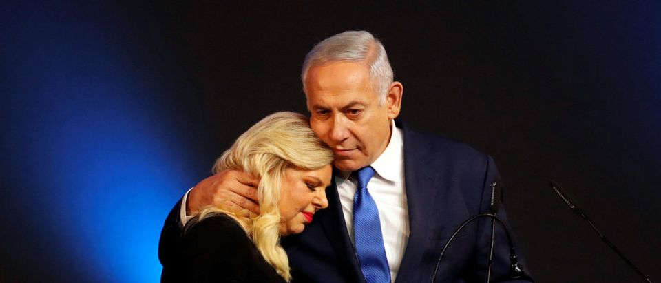 Israeli Prime Minister Benjamin Netanyahu hugs his wife Sara as they stand on stage following the announcement of exit polls in Israel's parliamentary election at the party headquarters in Tel Aviv, Israel April 10, 2019. REUTERS/Ronen Zvulun