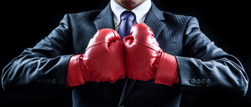 A businessman sports boxing gloves. Shutterstock image via aijiro