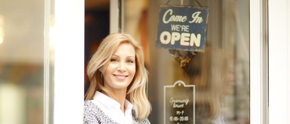 A female business owner stands outside her store. Shutterstock image via kinga