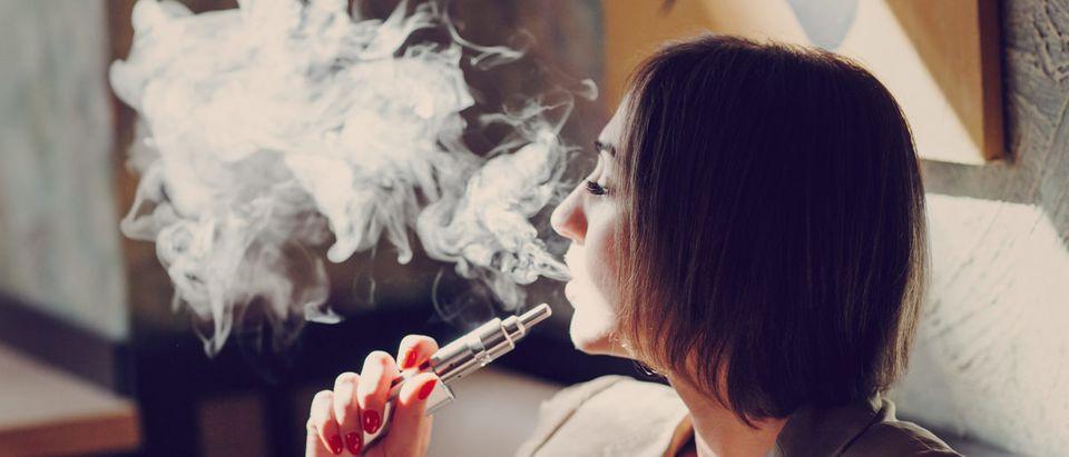 A woman smokes an e-cigarette. Shutterstock image via Oleggg