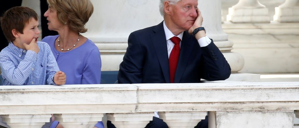 Former U.S. President Bill Clinton sits near a young boy and Kathleen Kennedy Townsend during a public memorial for Robert F. Kennedy at the 50th anniversary of his assassination at Arlington National Cemetery