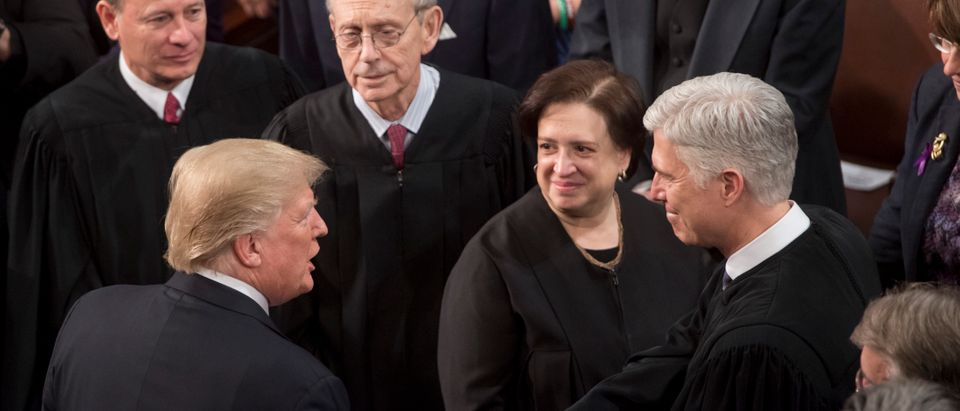 President Donald Trump shakes hands with Justice Neil Gorsuch as Chief Justice John Roberts, and Justices Stephen Breyer, and Elena Kagan look on before the State of the Union Address on January 30, 2018. (Saul Loeb/AFP/Getty Images)
