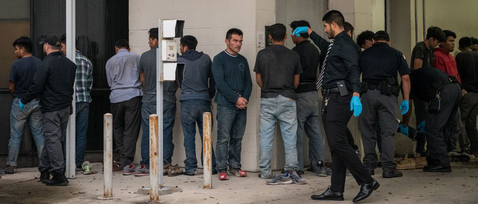 Shackled migrants in federal custody are searched upon arriving for immigration hearings at the US federal courthouse on June 12, 2019, in McAllen, Texas. (LOREN ELLIOTT/AFP/Getty Images)