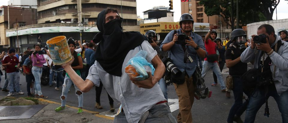 Protesters throw stones and other objects to the Venezuelan National Police during a demonstration called by opposition leader Juan Guaidó as part of the 208th anniversary of the Venezuelan Independence declaration on July 5, 2019 in Caracas, Venezuela. (Edilzon Gamez/Getty Images)