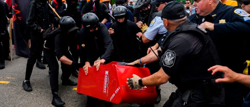 "Members of an anti-fascist or Antifa group drag a newspaper stand onto the street while they fight with police as the Alt-Right movement gathers for a ""Demand Free Speech"" rally in Washington, DC, on July 6, 2019. (ANDREW CABALLERO-REYNOLDS/AFP/Getty Images)"