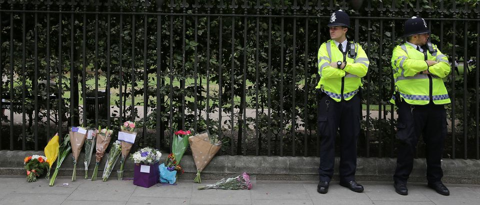 Police personnel stand beside floral tributes left in London's Russell Square on August 4, 2016, following an overnight stabbing spree that left one woman dead and five others injured. British police were holding a 19-year-old man on suspicion of murder Thursday after a central London stabbing spree that killed a US woman but appeared unrelated to terrorism. / AFP / DANIEL LEAL-OLIVAS (Photo credit should read DANIEL LEAL-OLIVAS/AFP/Getty Images)