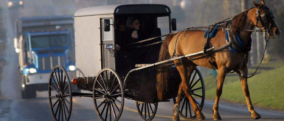An Amish buggy on the road in front of a truck. (Photo by William Thomas Cain/Getty Images)
