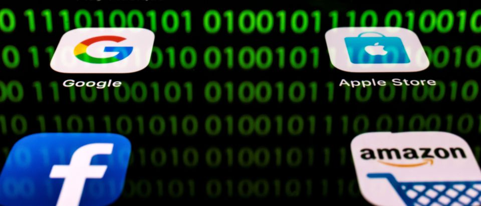 This illustration picture taken on April 20, 2018 in Paris shows apps for Google, Amazon, Facebook, Apple (GAFA) and the reflexion of a binary code displayed on a tablet screen. (LIONEL BONAVENTURE/AFP/Getty Images)