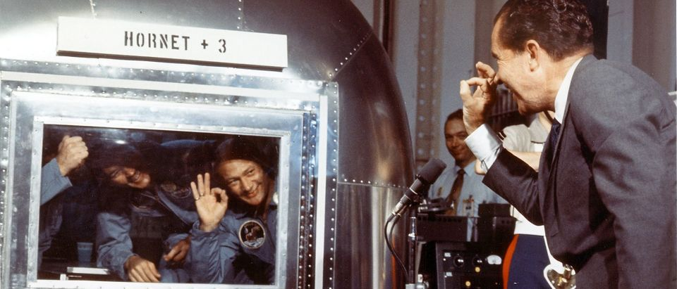 """President Richard M. Nixon and the Apollo 11 astronauts exchange """"A-OK signs"""" through the window of the Mobile Quarantine Facility 24 July 1969 aboard the USS Hornet. The astronauts, (L-R) Neil A. Armstrong, Michael Collins and Edwin E. Aldrin Jr splashed down in the Pacific Ocean at 12:50 p.m. EDT 24 July, 900 miles southwest of Hawaii at the completion of their successful lunar landing mission. AFP PHOTO NASA (Photo by NASA / NASA / AFP) (Photo credit should read NASA/AFP/Getty Images)"""