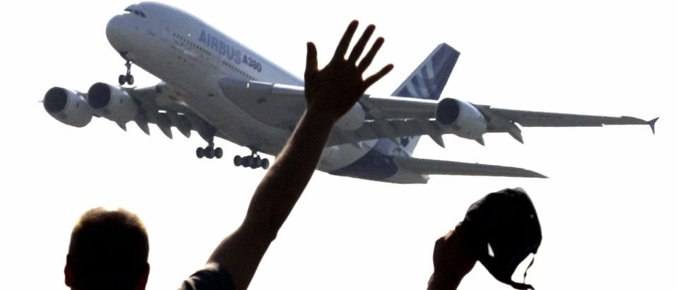 Spectators wave as they watch the world's biggest airliner, the Airbus A380, taking off on its ...