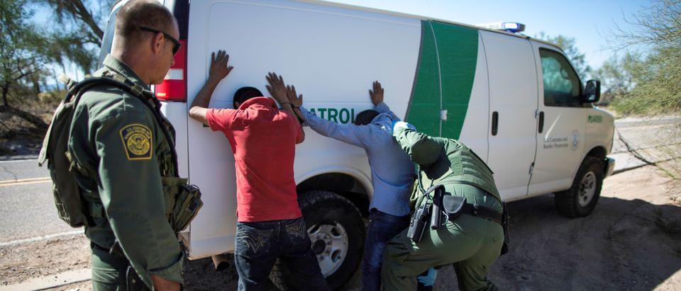 Border Patrol agents arrest migrants who crossed the U.S.-Mexico border in the desert near Ajo