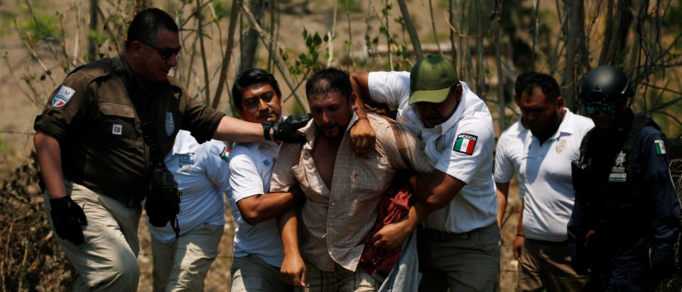 A Central American migrant is detained by Immigration officers during a raid on his journey towards the United States, in Pijijiapan, Mexico (REUTERS/Jose Cabezas)